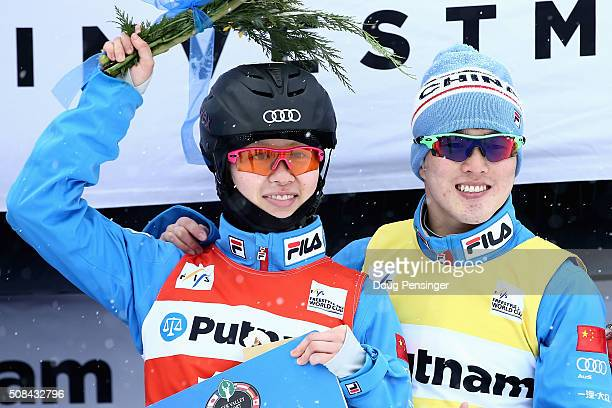 Yu Yang of China and Guangpu Qi of China celebrate on the podium after winning ladies' and men's FIS Freestyle Skiing Aerials World Cup at the Visa...