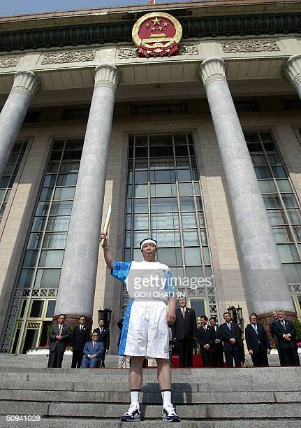 Yu Zaiqing China's member of the International Olympic Committee holds up the Olympic flame on the steps of the Great Hall of the People in Beijing...