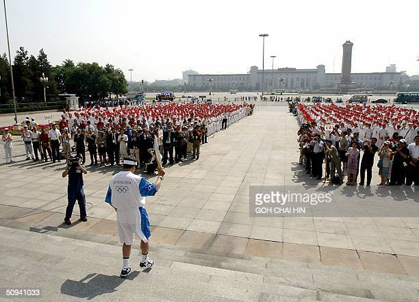 Yu Zaiqing China's member of the International Olympic Committee takes the Olympic flame down the steps of the Great Hall of the People in Beijing 09...