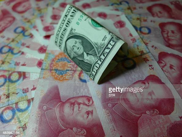Yuan banknotes and US dollars are seen on a table in Yichang central China's Hubei province on August 14 2015 China's central bank on August 14...