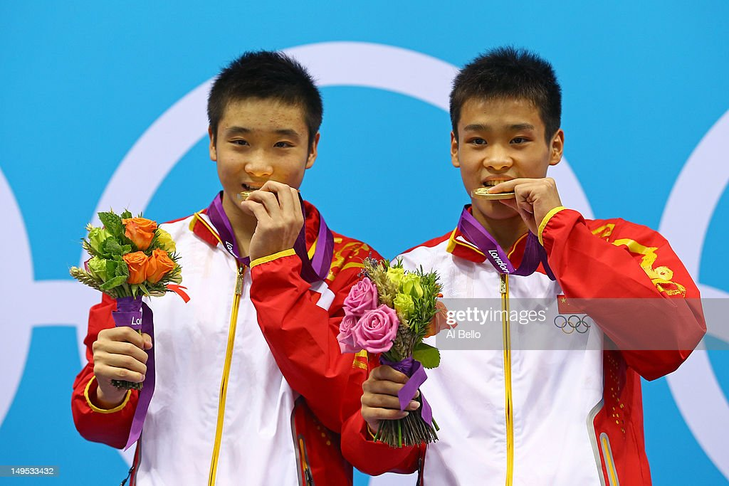 Yuan Cao and Yanquan Zhang of China celebrate with their gold medals during the medal ceremony for the Men's Synchronised 10m Platform Diving on Day 3 of the London 2012 Olympic Games at the Aquatics Centre on July 30, 2012 in London, England.