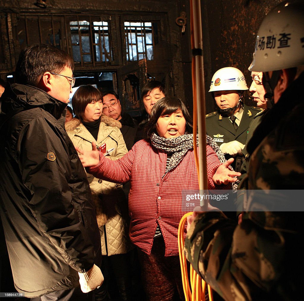 Yuan Lihai (C), the owner of a private orphanage, talks to rescuers and inspectors after a fire swept through the home for orphans and abandoned children in Lankao, in central China's Henan province on January 4, 2013. Seven children died and another was injured in the accident, local government and state media said. CHINA OUT AFP PHOTO