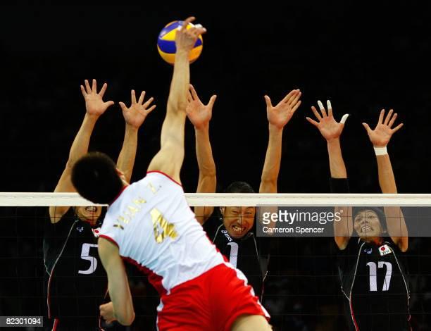 Yuan Zhi of China spikes the ball against Daisuke Usami Nobuharu Saito and Yu Koshikawa of Japan during the volleyball event held at the Institute of...