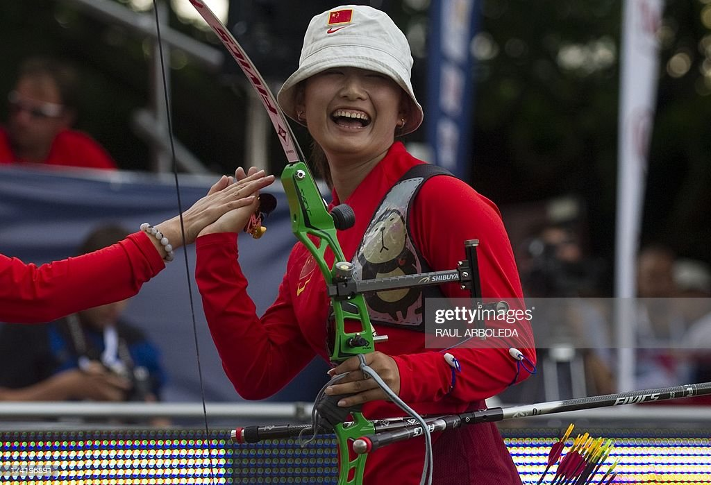 Yuanyuan Cui of China celebrates with her coach after winning the bronze medal in the Archery World Cup recurve women individual final competition against Sara Lopez of Colombia in Medellin, Antioquia department, Colombia on July 21, 2013. AFP PHOTO/Raul ARBOLEDA