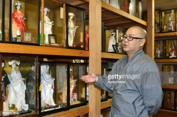 Yuchi Shiroto chief priest of Koboji a Buddhist temple known for rare 'marriage' rites for people who died single speaks in front of glass containers...