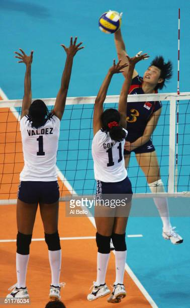 Yudelkys Bautista of China spikes against Annerys Valdez Vargas and Juanna Sanchez Gonzalez of the Dominican Republic in the women's indoor...