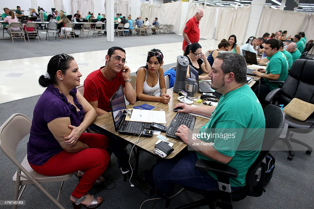 Yudelmy Cataneda, Javier Suarez and Claudia Suarez (L-R) sit with, Yosmay Valdivian, an insurance agent from Sunshine Life and Health Advisors as they and others try to purchase health insurance under the Affordable Care Act at a store setup in the Mall of Americas on March 20, 2014 in Miami, Florida. The owner of Sunshine Life and Health Advisors, Odalys Arevalo, said she has seen a surge in people, some waiting up to 3 hours or more in line, trying to sign up for the Affordable Care Act before the open enrollment period for individual insurance ends on March 31.