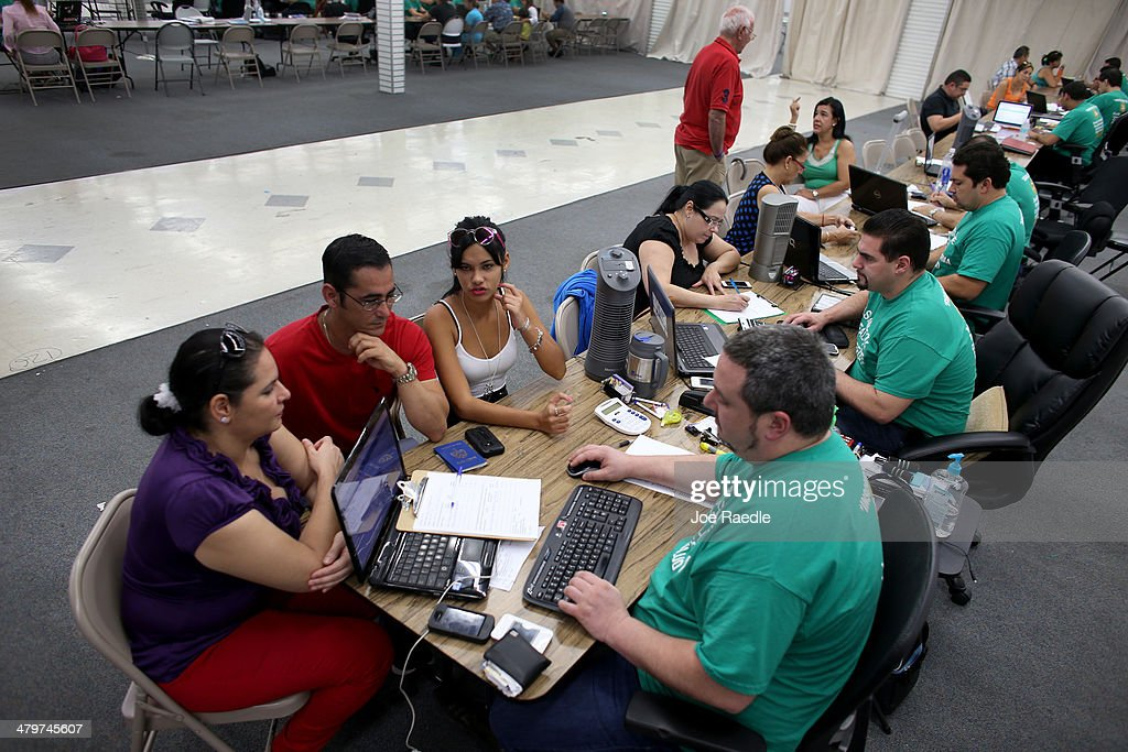 Yudelmy Cataneda, Javier Suarez and Claudia Suarez sit with, Yosmay Valdivian, an insurance agent from Sunshine Life and Health Advisors as they and others try to purchase health insurance under the Affordable Care Act at a store setup in the Mall of Americas on March 20, 2014 in Miami, Florida. The owner of Sunshine Life and Health Advisors, Odalys Arevalo, said she has seen a surge in people, some waiting up to 3 hours or more in line, trying to sign up for the Affordable Care Act before the open enrollment period for individual insurance ends on March 31.