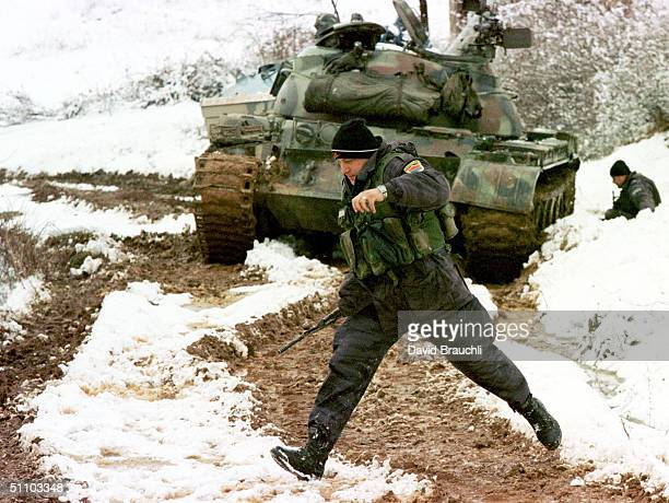 A Yugoslav Special Forces Policeman Runs After Coming Under Fire From Opposing Kosovo Liberation Army Forces Tuesday Feb 23 1999 In The Village Of...
