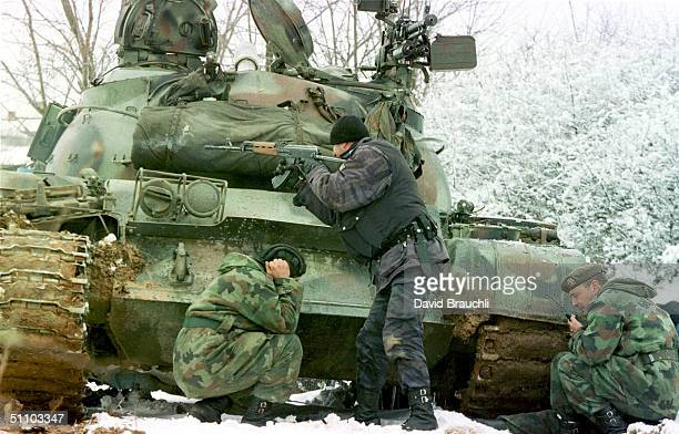 Yugoslav Special Forces Policeman Shoots His Rifle At Opposing Kosovo Liberation Army Forces As A Yugoslav Army Tank Driver Covers His Ears After...