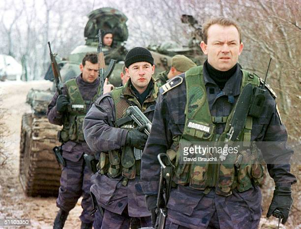 Yugoslav Special Forces Policemen Walk Away From The Front Line After A FireFight With Opposing Kosovo Liberation Army Forces As A Yugoslav Army Tank...