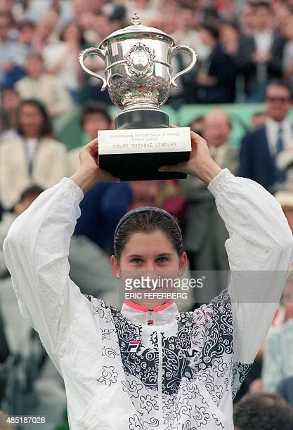 Yugoslavian tennis player Monica Seles holds up the Winner's Trophy after defeating German Steffi Graf on June 6 1992 at Roland Garros Stadium during...