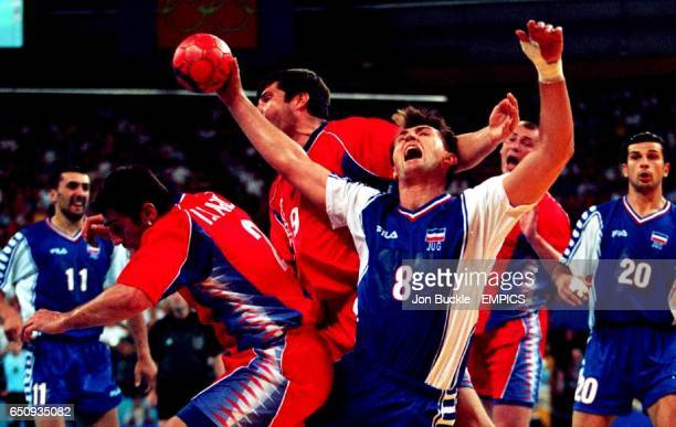 Yugoslavia's Nedeljko Jovanovic is muscled out of a shooting position by Russia's Igor Lavrov and Vassili Koudinov