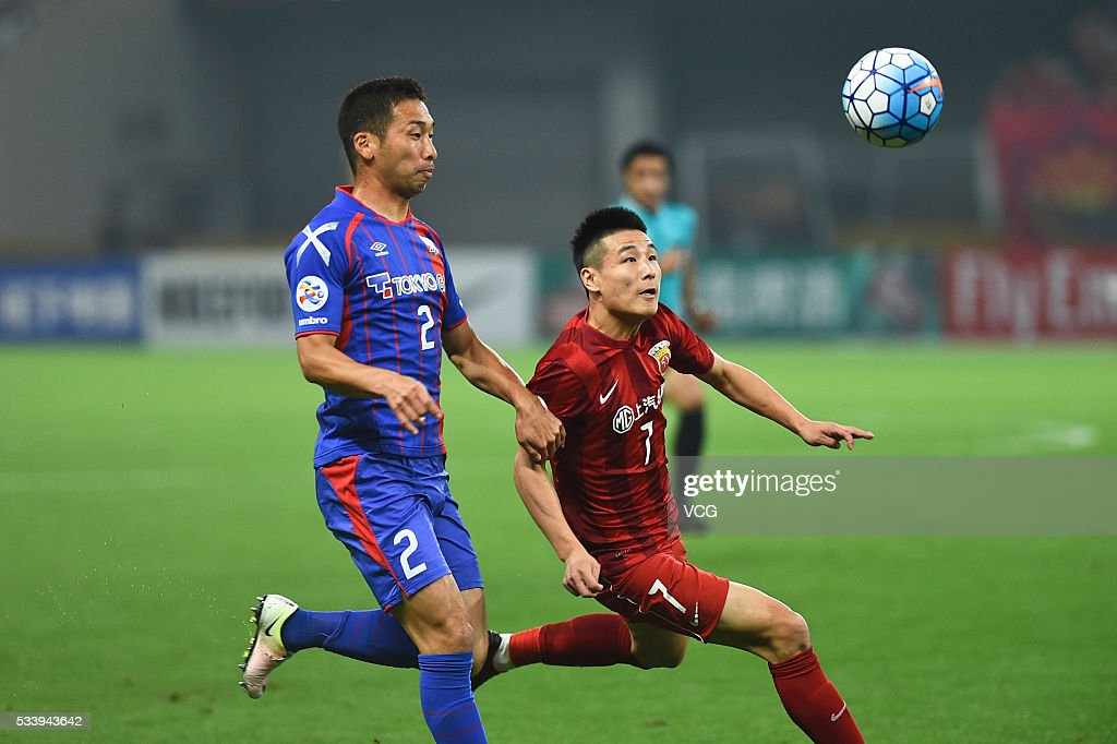 Yuhei Tokunaga #2 of FC Tokyo and Wu Lei #7 of Shanghai SIPG compete for the ball during the 1/8 match of AFC Asia Champions League between Shanghai SIPG and FC Tokyo at Shanghai Stadium on May 24, 2016 in Shanghai, China.