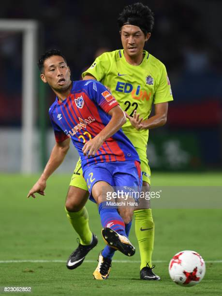 Yuhei Tokunaga of FC Tokyo and Yusuke Minagawa of Sanfrecce Hiroshima compete for the ball during the JLeague Levain Cup PlayOff Stage first leg...