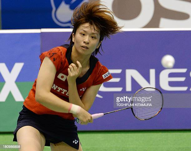 Yui Hashimoto of Japan hits a return during her women's singles second round match against Aya Ohori of Japan at the Japan Open 2013 badminton...