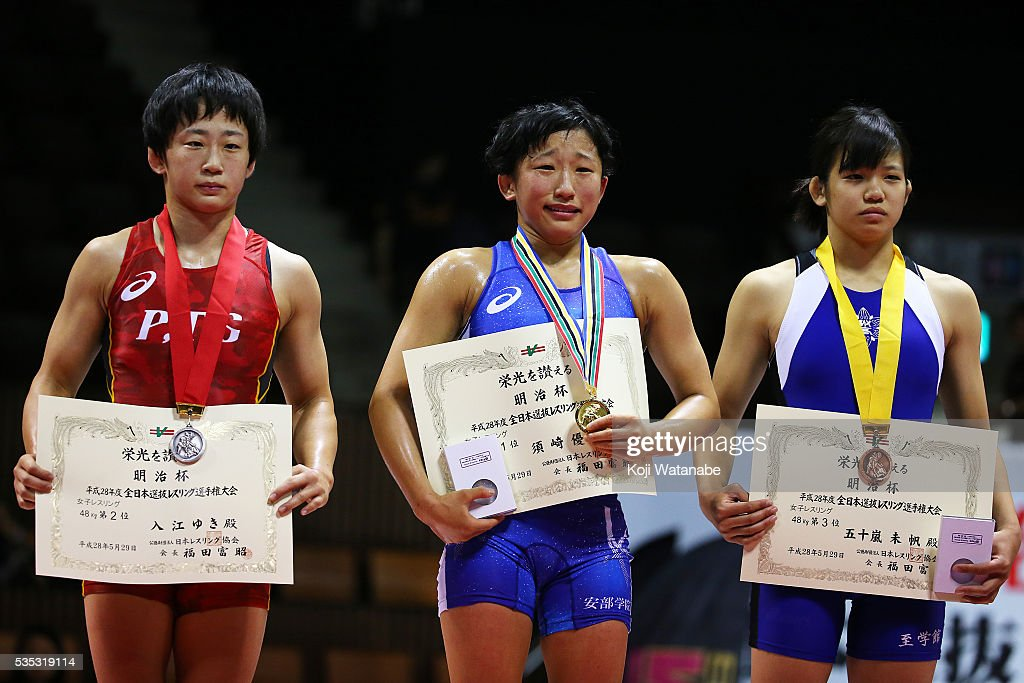 Yui Suzaki (C) celebrates at the award ceremony for the Women's 48kg free style final match during the All Japan Wrestling Championships at Yoyogi National Gymnasium on May 29, 2016 in Tokyo, Japan.