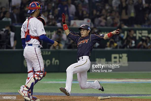 Yuichi Honda of Japan slides into home base to score in the eighth inning during the World Baseball Classic Second Round Pool 1 game between Japan...