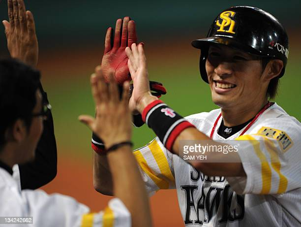 Yuichi Honda of Japan's champions Softbank Hawks celebrates with his team after running back to the home base against South Korea's champions Samsung...