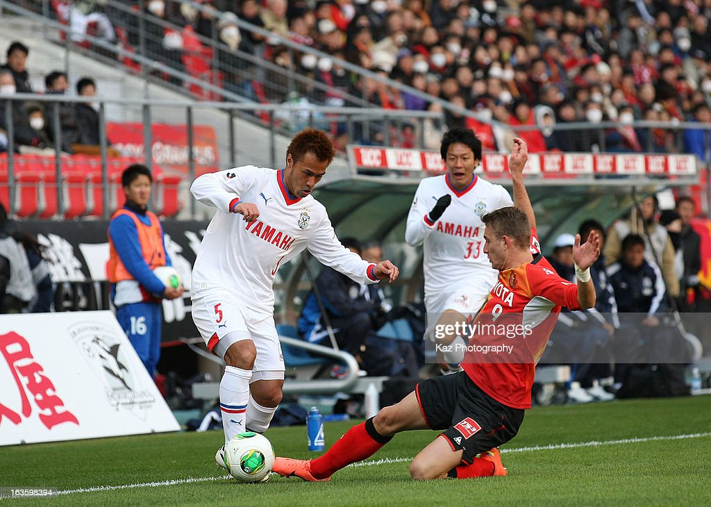 Yuichi Komano of Jubilo Iwata is tackled by Nikola Jakimovski of Nagoya Grampus during the J.League match between Nagoya Grampus and Jubilo Iwata at Toyota Stadium on March 2, 2013 in Toyota, Aichi, Japan.