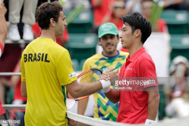 Yuichi Sugita of Japan and Guilherme Clezar of Brazil shake hands after their singles match during day one of the Davis Cup World Group Playoff...