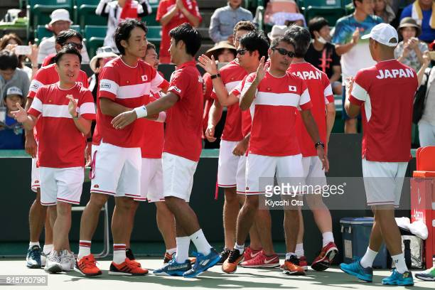 Yuichi Sugita of Japan celebrates the team's 31 victory with Go Soeda of Japan and team staff after winning his singles match against Thiago Monteiro...