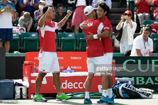 Yuichi Sugita of Japan celebrates the team's 31 victory with team captain Satoshi Iwabuchi of Japan after winning his singles match against Thiago...
