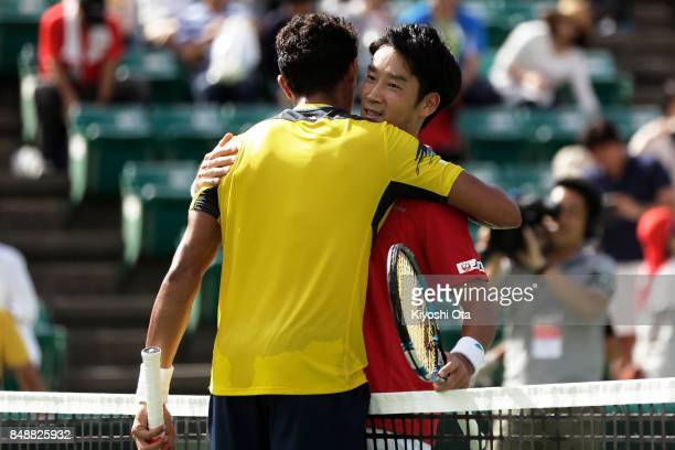 Yuichi Sugita of Japan embraces Thiago Monteiro of Brazil after their singles match during day four of the Davis Cup World Group Playoff between...