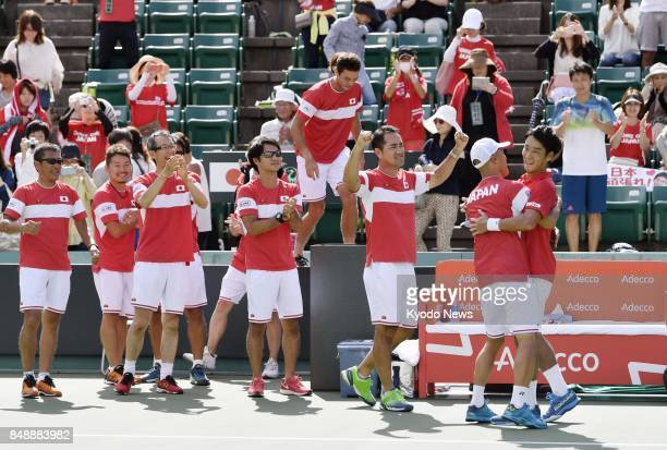 Yuichi Sugita of Japan is congratulated by his teammates after defeating Thiago Monteiro of Brazil 63 62 63 in the first reverse singles match in a...