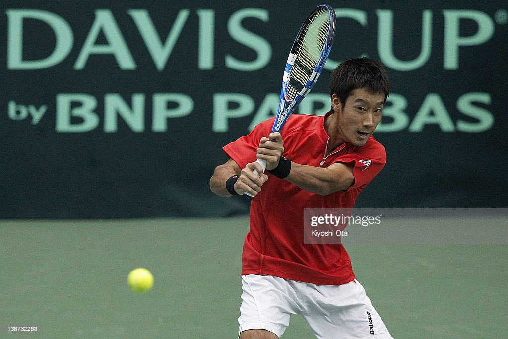 Yuichi Sugita of Japan plays a backhand as he plays with his teammate Tatsuma Ito in their doubles match against Ivo Karlovic and Ivan Dodig of...