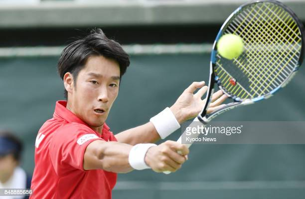 Yuichi Sugita of Japan plays a backhand in his match against Thiago Monteiro of Brazil in the first reverse singles in a Davis Cup World Group...