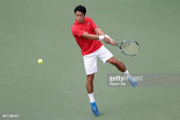 Yuichi Sugita of Japan plays a backhand in his singles match against Guilherme Clezar of Brazil during day one of the Davis Cup World Group Playoff...