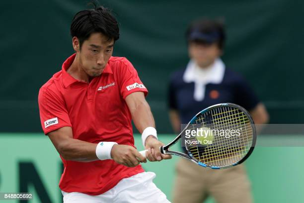 Yuichi Sugita of Japan plays a backhand in his singles match against Thiago Monteiro of Brazil during day four of the Davis Cup World Group Playoff...