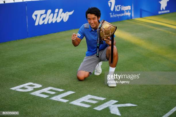 Yuichi Sugita of Japan receives his trophy after defeating Adrian Mannarino of France during their men's final match of ATP World Tour 250 Antalya...