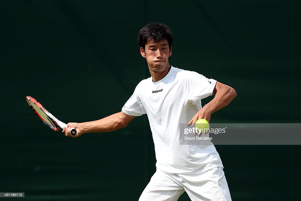 Yuichi Sugita of Japan returns a shot during his Gentlemen's Singles first round match against Feliciano Lopez of Spain on day two of the Wimbledon...