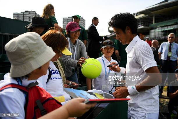 Yuichi Sugita of Japan signs autographs after victory in the Gentlemen's Singles first round match against Brydan Klein of Great Britain on day two...