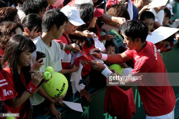 Yuichi Sugita of Japan signs autographs for fans after the team's 31 victory against Brazil during day four of the Davis Cup World Group Playoff...