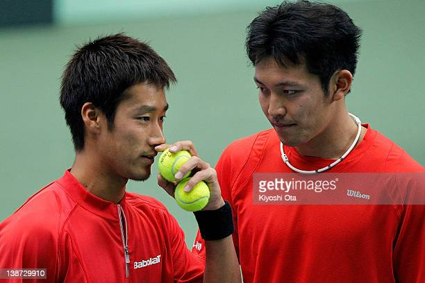 Yuichi Sugita speaks to his teammate Tatsuma Ito in their doubles match against Ivo Karlovic and Ivan Dodig of Croatia during day two of the Davis...