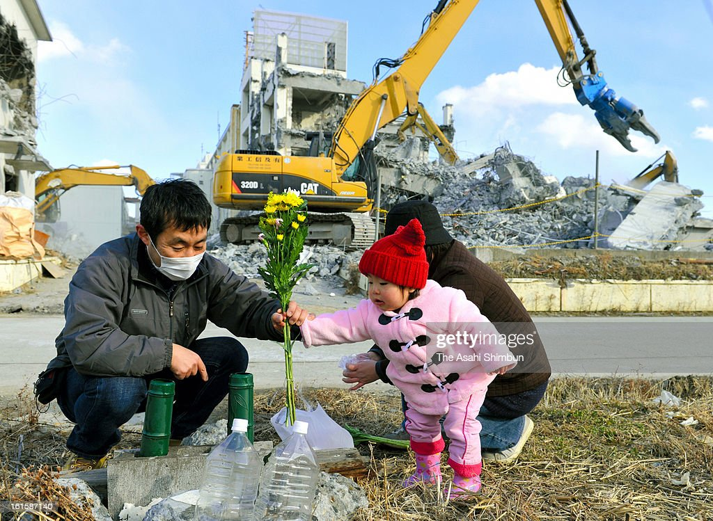 Yuichi Yonezawa (L) and his daughter Tae offer a flower bunch at his house used to stand on February 11, 2013 in Rikuzentakata, Iwate, Japan. 2 year anniversary approaches though the restoration from the earthquake and tsunami have been delayed.
