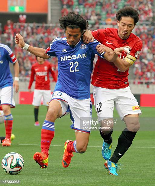 Yuji Nakaazawa of Yokohama FMarinos and Yuki Abe of the Urawa Red Diamonds compete for the ball during the JLeague match between Urawa Red Diamonds...