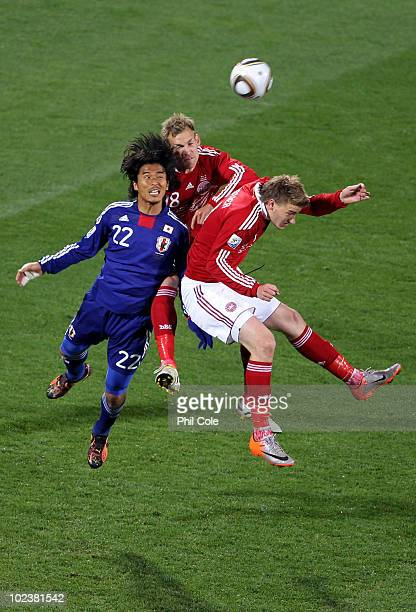 Yuji Nakazawa of Japan jumps with Soren Larsen and Nicklas Bendtner of Denmark during the 2010 FIFA World Cup South Africa Group E match between...