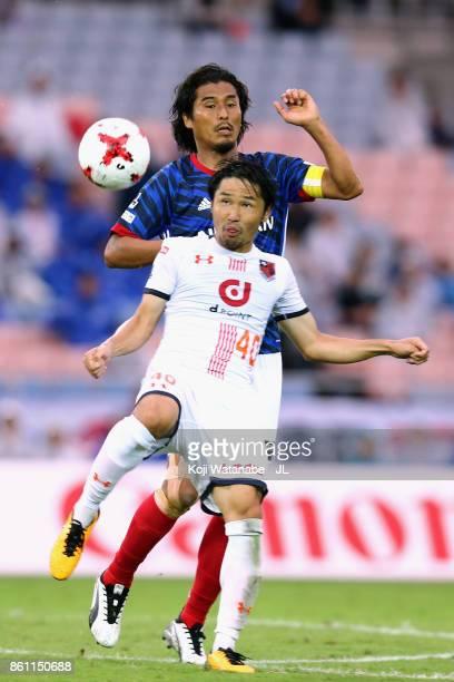 Yuji Nakazawa of Yokohama FMarinos and Akimi Barada of Omiya Ardija compete for the ballduring the JLeague J1 match between Yokohama FMarinos and...