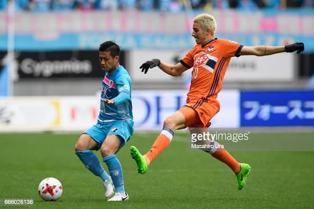 Yuji Ono of Sagan Tosu controls the ball under pressure of Thiago Galhardo of Albirex Niigata during the JLeague J1 match between Sagan Tosu and...