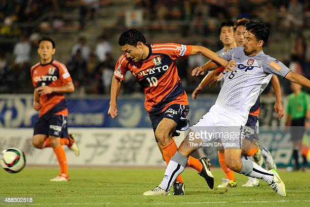 Yuji Senuma of Ehime FC and Tadashi Takeda of Fagiano Okayama compete for the ball during the JLeague second division match between Ehime FC and...