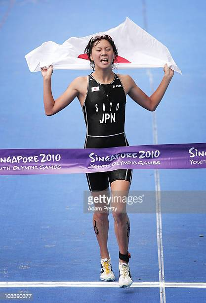 Yuka Sato of Japan croses the finish line in first place winning the first Gold Medal of the 2010 Yoth Olympics in the Womens Triathlon on day one of...