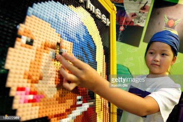 Yuka Takahashi attaches the last piece of Lego bricks to a replica of Johannes Vermeer's 'Girl with a Pearl Earring' for the final touch during an...