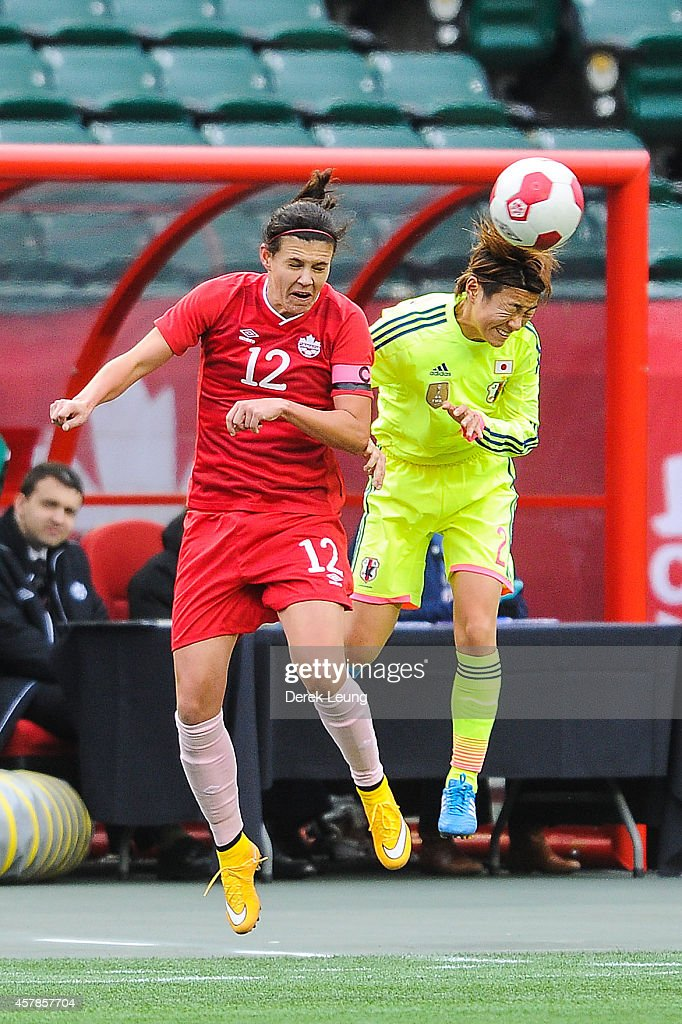 Yukari Kinga of Japan jumps for a header against Christine Sinclair #12 of Canada during a match at Commonwealth Stadium on October 25, 2014 in Edmonton, Alberta, Canada.