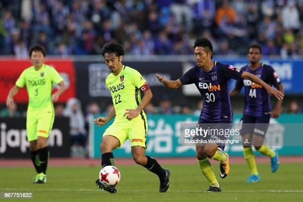 Yuki Abe of Urawa Red Diamonds and Kosei Shibasaki of Sanfrecce Hiroshima compete for the ball during the JLeague J1 match between Sanfrecce...