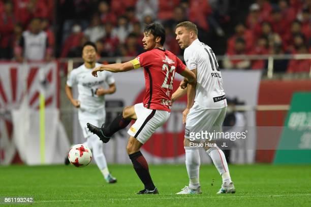 Yuki Abe of Urawa Red Diamonds and Lukas Podolski of Vissel Kobe compete for the ball during the JLeague J1 match between Urawa Red Diamonds and...