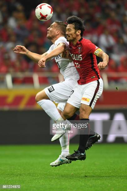 Yuki Abe of Urawa Red Diamonds and Lukas Podolski of Vissel Kobe compete for theball during the JLeague J1 match between Urawa Red Diamonds and...